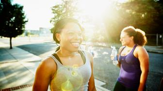 Smiling woman drinking water after morning run with friends