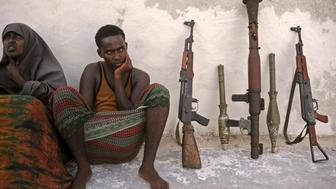 Suspected Al Qaeda-aligned Shabaab militants, a woman and one of her children, sit next to weapons after their arrest on May 5, 2016 in Mogadishu. Somali security forces presented to journalists a family suspected of belonging to the Somalia-based al-Qaeda affiliated Islamist militant group Al-Shabaab. Members of this family were arrested with two AK-47 assault rifles and a rocket during an operation by Somali security forces against suspected members of of Somalia's Shebab Islamists in the capital Mogadishu. / AFP / MOHAMED ABDIWAHAB        (Photo credit should read MOHAMED ABDIWAHAB/AFP/Getty Images)