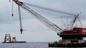 A construction crane floats next to a barge carrying jacket support structures and a platform for a turbine for a wind farm in the waters of the Atlantic Ocean off Block Island, Rhode Island July 27, 2015. Deepwater Wind, a planned five-turbine, 30-megawatt wind farm off the coast of Block Island, would be North America's first offshore wind farm, a milestone the company says could pave the way for an industry long established in Europe but still struggling with opposition in the United States.        REUTERS/Brian Snyder