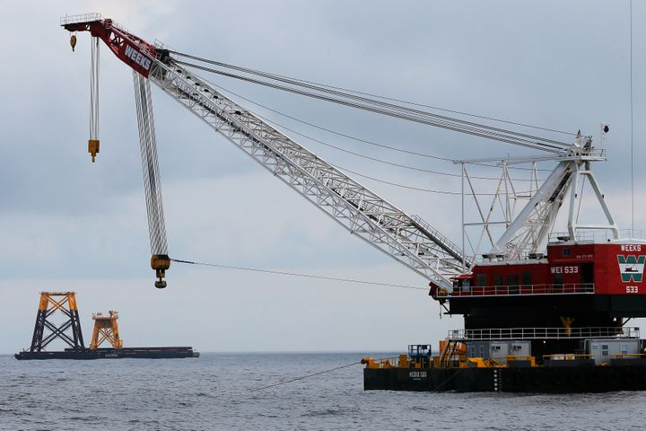 A construction crane floats next to a barge carrying jacket support structures and a platform for a turbine for a wind farm i
