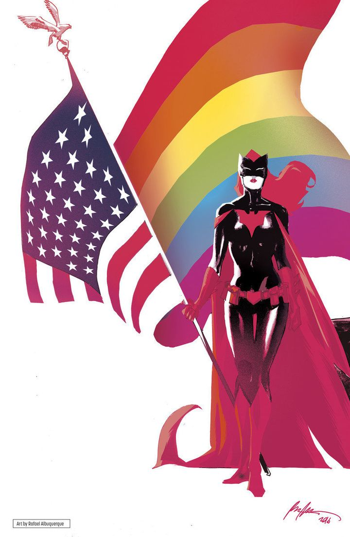 Batwoman holds an American flag with an LGBTQ flag waving behind her.