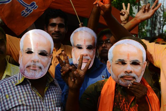 Indians wear masks bearing Modi's image as they celebrate the BJP's election result. Siliguri, India....