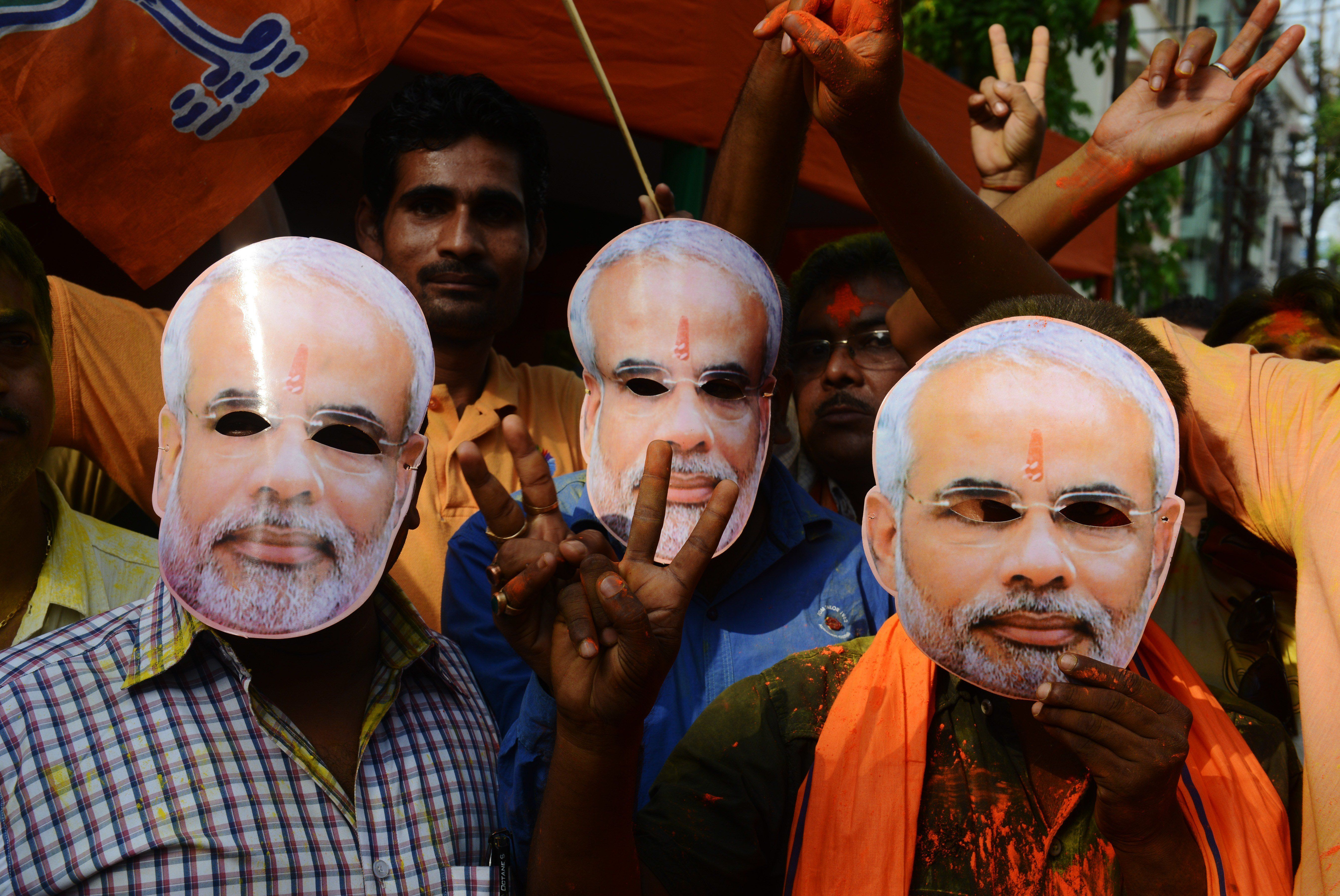 Indians wear masks bearing Modi's image as they celebrate the BJP's election result. Siliguri, India. May 16, 2014.
