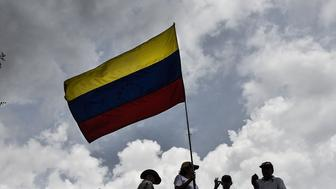 Opposition supporters hold a Venezuelan flag during a protest against the suspended recall referendum process on Francisco Fajardo Highway in Caracas, Venezuela, on Wednesday, Oct. 26, 2016. Venezuela's opposition upped the ante in its dispute with the government, calling a nationwide strike for Friday and a new march to the presidential palace next week if the government doesn't allow a recall referendum against President Nicolas Maduro to advance. Photographer: Carlos Becerra/Bloomberg via Getty Images