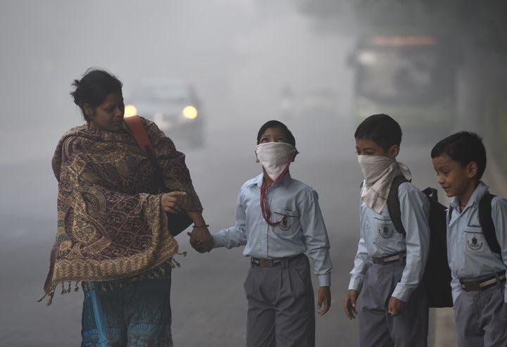 Schoolchildren cover up against the heavy smog inNew Delhi, India, on Nov. 3, 2016.