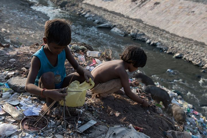 Indian boys sort through waste on the banks of a tributary flowing into the heavily polluted Ganges River. Varanasi, India. S