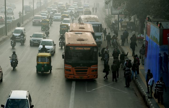 Indian commuters wait for their ride at a bus stop (R) where air purifiers have been installed in New Delhi on December 27, 2