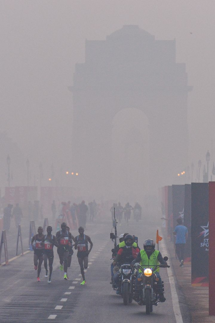 Participants run on Rajpath in front of India Gate, obscured by fog and smog, at the Delhi Half Marathon in New Delhi on Nove