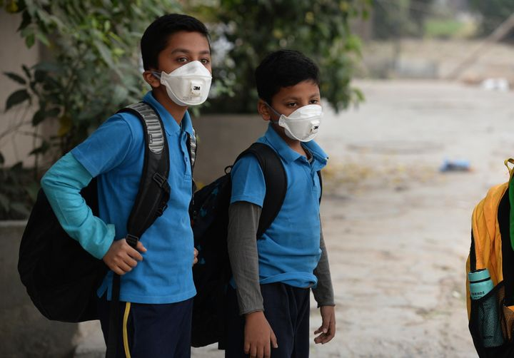 ndian school children wear masks as they wait for the bus as schools re-open after three days of closure due to smog, in New