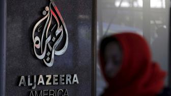 A woman passes by the Al Jazeera America broadcast center in midtown Manhattan in New York City January 13, 2016. Al Jazeera America, the cable television news outlet owned by Qatar-based Al Jazeera Media Network, is shutting down less than three years after its high-profile launch, the network said on Wednesday. REUTERS/Brendan McDermid