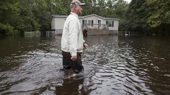 David Carroll of Waccamaw Lake Drive walks down his flood covered road to meet family in Conway, South Carolina October 6, 2015. Carroll has been living with several feet of water around his home since Saturday. Fourteen people have died amid historic rainfall in South Carolina, the state's governor said on Tuesday, as residents grappled with the damage wrought by flooding on their homes, roads and water supply. REUTERS/Randall Hill