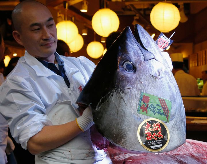 An employee holds the head of a 489-pound bluefin tuna outside Tsukiji fish market in Tokyo on Jan. 5, 2013.