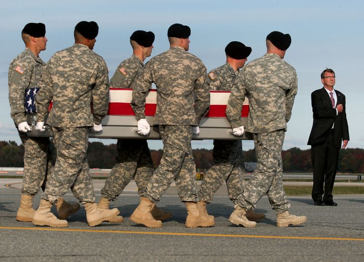 Secretary of Defense Ashton Carter stands at attention while an Army team transfers the remains of Master Sgt. Joshua L. Whee