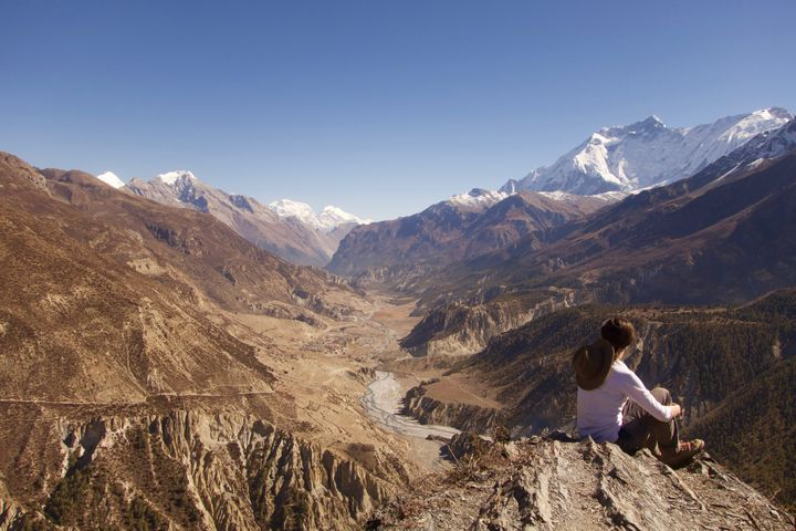 A trekker takes in the view of Manang Valley along the Annapurna Circuit in the Nepalese Himalayas.