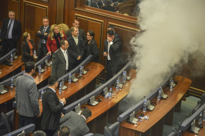 Kosovo parliamentary lawmakers step back as tear gar fills the chamber at Kosovo's parliament in Pristina on October 23, 2015