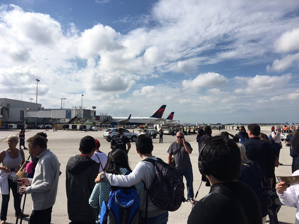 People wait on the Tarmac at Fort Lauderdale-Hollywood International Airport after a reported shooting