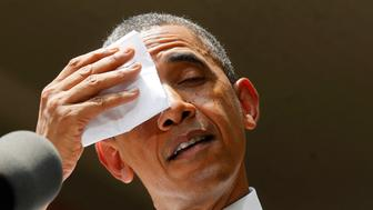 U.S. President Barack Obama pauses and wipes his forehead as he speaks about his vision to reduce carbon pollution while preparing the country for the impacts of climate change while at Georgetown University in Washington, June 25, 2013.        REUTERS/Larry Downing  (UNITED STATES - Tags: POLITICS ENVIRONMENT)