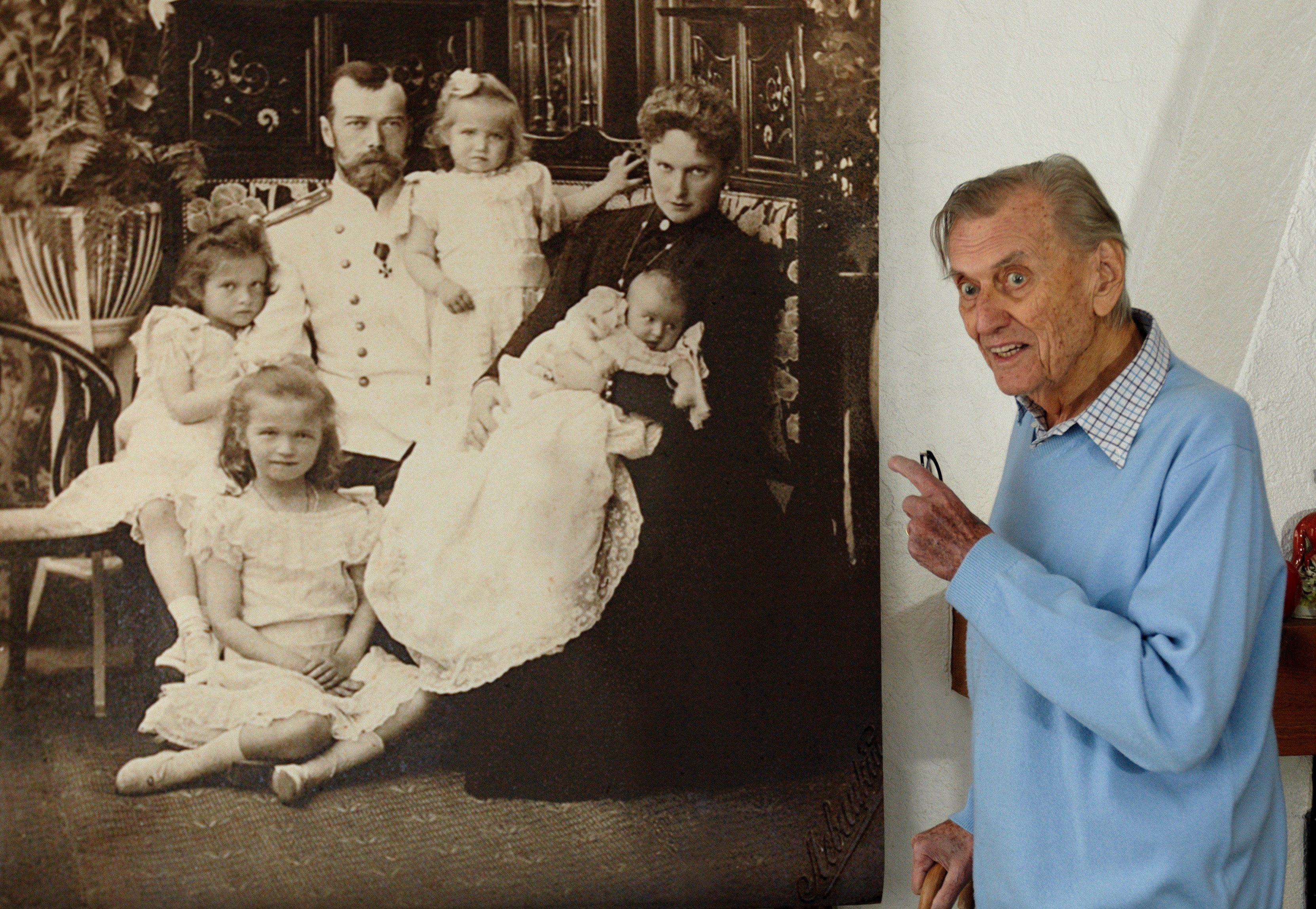 Prince Nicolas Romanov of Russia gestures in front of a enlarged photograph showing his ancestor Tsar Nicholas II, his wife Alexandra Fedorovna and their four daughters during an auction preview in his apartment in Rougemont, 150 km (93.2 miles) east of Geneva, November 29, 2012. Some 3000 items, including many photographs and letters of the last Tsar Nicholas II, will be offered for sale during an auction in Geneva December 10 to 13. REUTERS/Denis Balibouse (SWITZERLAND - Tags: SOCIETY ROYALS)