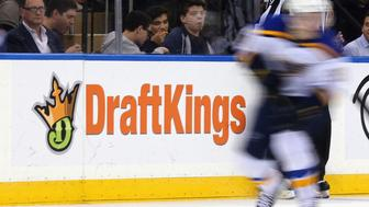 NEW YORK, NY - NOVEMBER 12:  The New York Rangers and St. Louis Blues skate in front of a dasher board advertising the betting website DraftKings at Madison Square Garden on November 12, 2015 in New York City.  (Photo by Bruce Bennett/Getty Images)