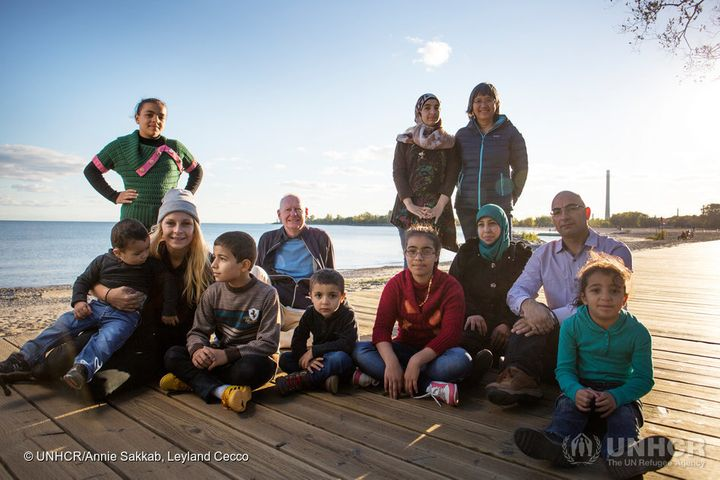 Mohamed Nouman (bottom right) poses with his family and sponsors Thuy Nguyen and Michael Adams on the boardwalk of a Toronto