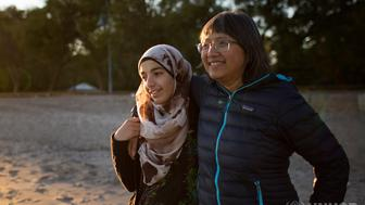Thuy Nguyen and Narjes Nouman spend time at a beach in downtown Toronto. Ms. Nguyen arrived as a refugee more than forty years ago and now serves as a mentor to newly arrived Narjes. ; From coast to coast, Canadians continue to show an outpouring of support for Syrian refugees. By housing them and including them as members of the community, they create powerful, if unlikely, bonds of friendship.  From Far and Wide profiles the diverse group stepping up to welcome these families, unbound by geography or language. In Toronto, a former Vietnamese refugee develops a close relationship with a young Syrian girl, seeing much of herself in the teenager. High up north, a community group in the Yukon takes on a family of 11, teaching them fishing and skating. Across this vast country, friends and strangers set a global example.   Some spend their time teaching English, others take families for walks in the park— all work unified by the belief that strong communities elevates all Canadians.  These images are of the Nouman family where a group of sponsors work closely with the family to help in the resettlement process in Toronto, Canada. The sponsor group organizes social outings, errands and shopping for the family.