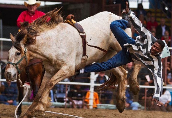 An inmate falls off a horse during the Angola Rodeo.