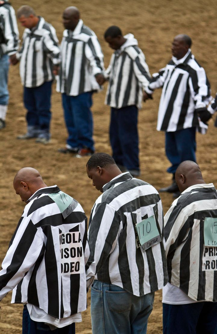 Inmates hold hands during a prayer at the Angola Rodeo.