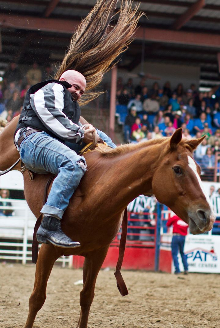 An inmate tries to hold on to a horse during the Angola Rodeo.