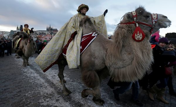 Men dressed as the Three Kings greet spectators as they ride camels during the Three Kings procession across the medieval Cha
