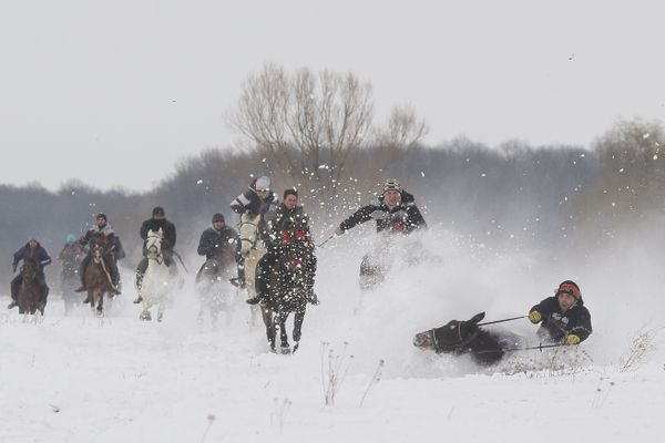 A horse and a rider fall in the snow during a race that followed the celebration of an Epiphany religious service, in Pietros