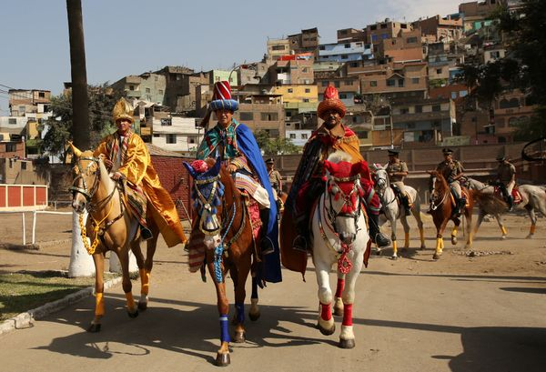 Peruvian policemen dressed as the Three Kings greet spectators as they ride horses during Epiphany celebrations, or Three Kin