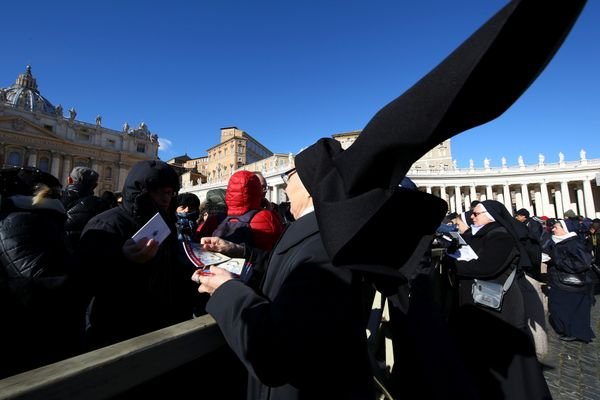 "A nun distributes books titled ""Icons of Mercy"" donated by Pope Francis to the faithful on Epiphany day in Saint Peter's Squa"