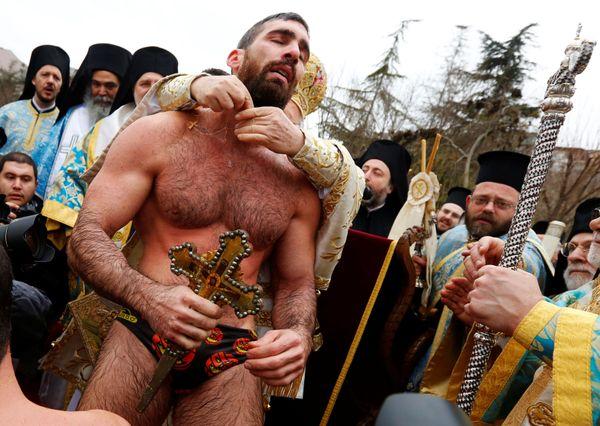 Greek Orthodox faithful Nikolas Solis, 29, a pilgrim from Greece, receives a gift from Greek Orthodox Ecumenical Patriarch Ba