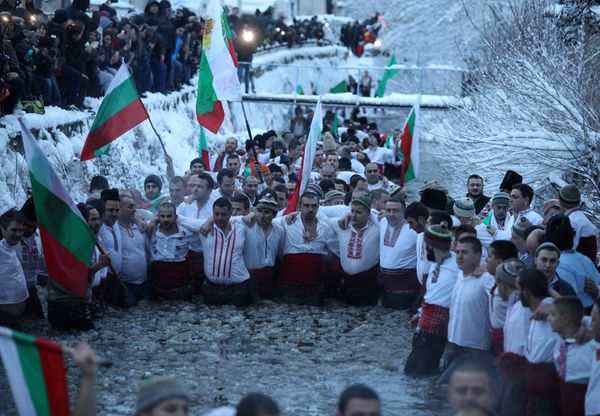 Bulgarian men dance in the icy waters of the Tundzha river during a celebration to commemorate Epiphany Day in the town of Ka
