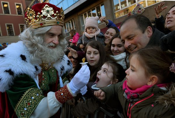 A man dressed as one of the Three Kings receives a baby pacifier from a girl during the Epiphany parade in Gijon, Spain Janua