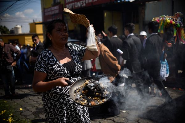 A woman burns incense in honor of the Three Wise Men or Three Kings celebration on Epiphany at El Guarda Viejo neighborhood i