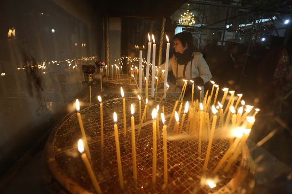 People light candles during celebrations of Jesus Christ's baptism and birth at Church of the Nativity in Bethlehem, West Ban
