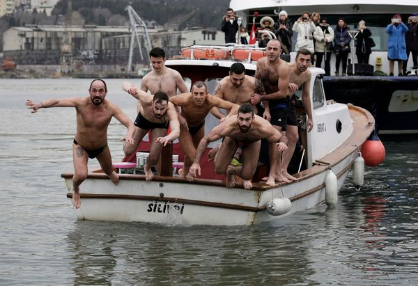 Members of the Orthodox Church jump into the the Bosphorus to recover a wooden cross and be blessed, on the occasion of the c