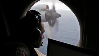 Flight officer Rayan Gharazeddine looks out of a Royal Australian Air Force (RAAF) AP-3C Orion as it flies over the southern Indian Ocean during the search for missing Malaysian Airlines flight MH370 March 22, 2014.  REUTERS/Rob Griffith/Pool/File Photo