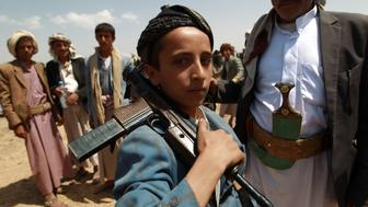 An Armed Yemeni boy loyal to the Shiite Huthi movement poses for a picture during a tribal gathering against al-Qaeda militants in the Bani al-Harith area, north of Sanaa, on August 17, 2014. Yemen faces multiple domestic problems, including ongoing insecurity and insurgencies posed by Shiite Houthi fighters, southern separatists and the al-Qaeda in the Arabian Peninsula (AQAP).  AFP PHOTO / MOHAMMED HUWAIS        (Photo credit should read MOHAMMED HUWAIS/AFP/Getty Images)