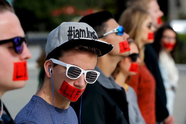 "Members of the anti-abortion protest group Bound 4 Life wear red tape over their mouths reading ""Life"" as they demonstrate at"