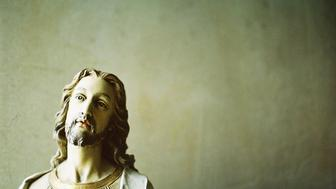 A Jesus figurine in front of the wall.