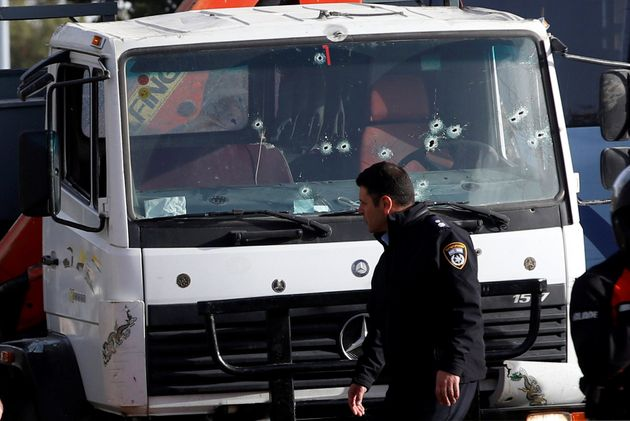 An Israeli policeman walks at the scene of a truck-ramming incident in Jerusalem January 8,