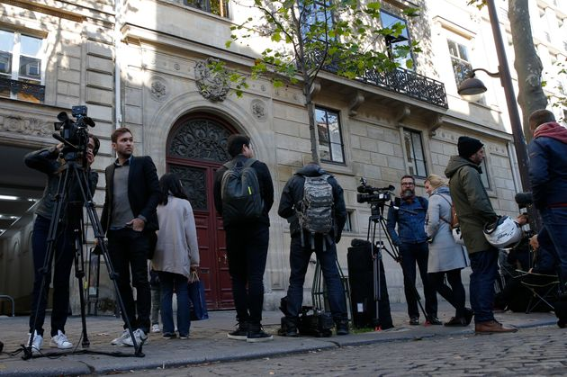 Journalists stand in front of the entrance of a luxury residence on the Rue Tronchet in central Paris...