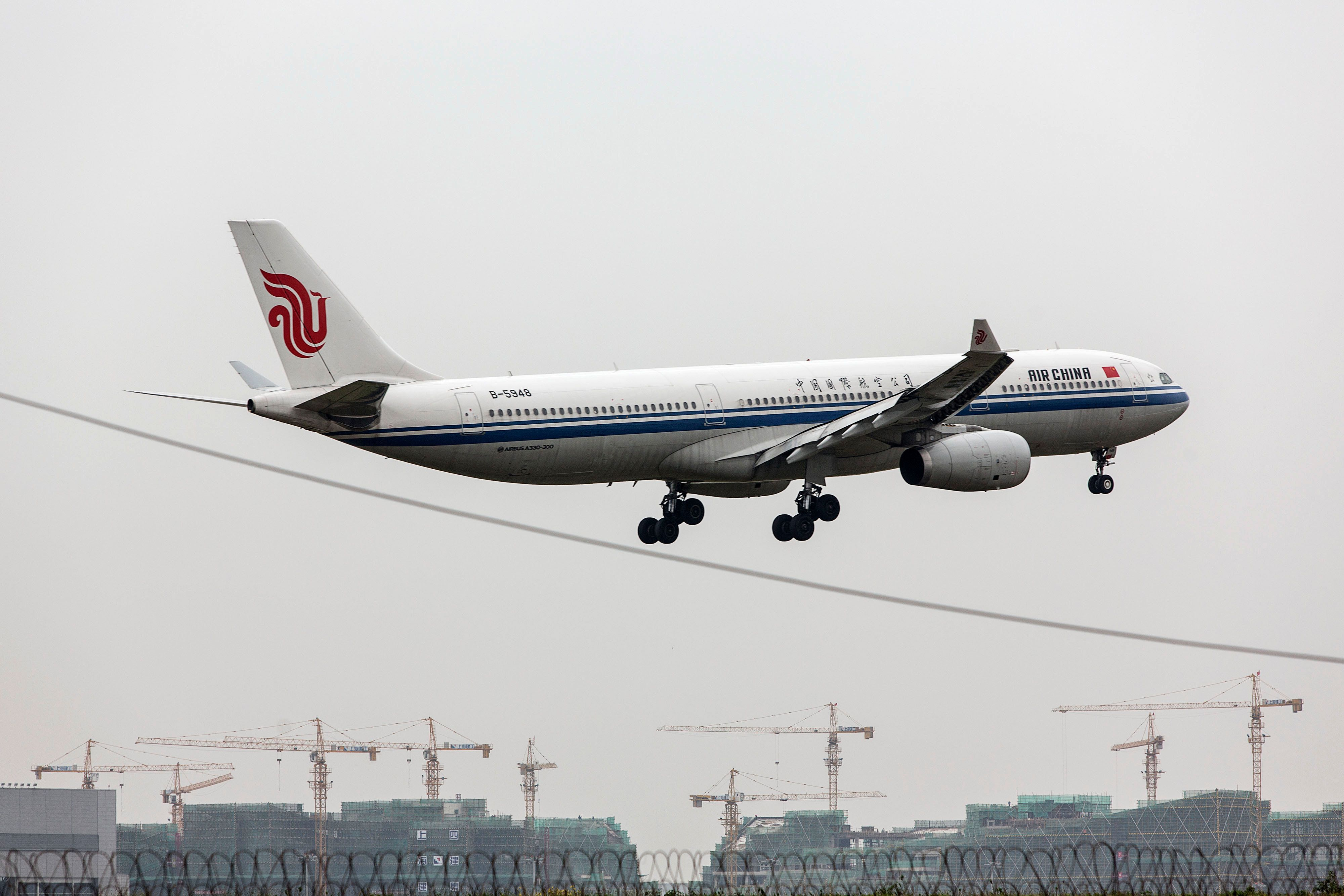 An Air China Ltd. aircraft flies over cranes operating at construction sites as it approaches to land at Hongqiao Airport in Shanghai, China, on Friday, Oct. 23, 2015. China is considering combining some operations of the nations three biggest airlines as part of a broad reform of its state-owned enterprises, people familiar with the plans said. Photographer: Qilai Shen/Bloomberg via Getty Images