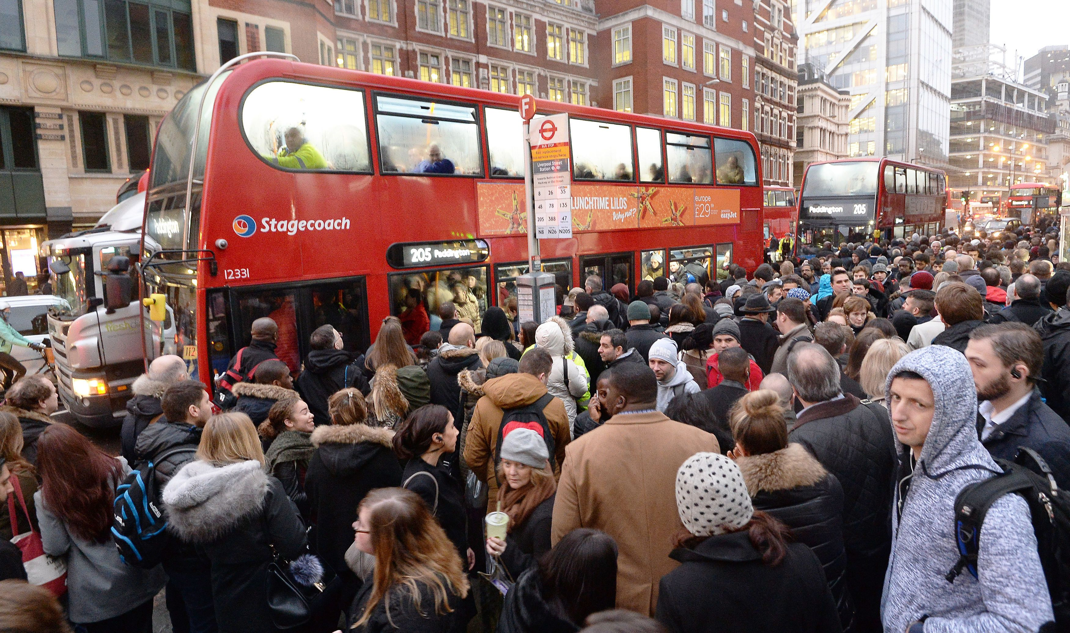 Commuters queue for buses at London's Bishopsgate at a 24-hour Tube strike led to transport chaos across...