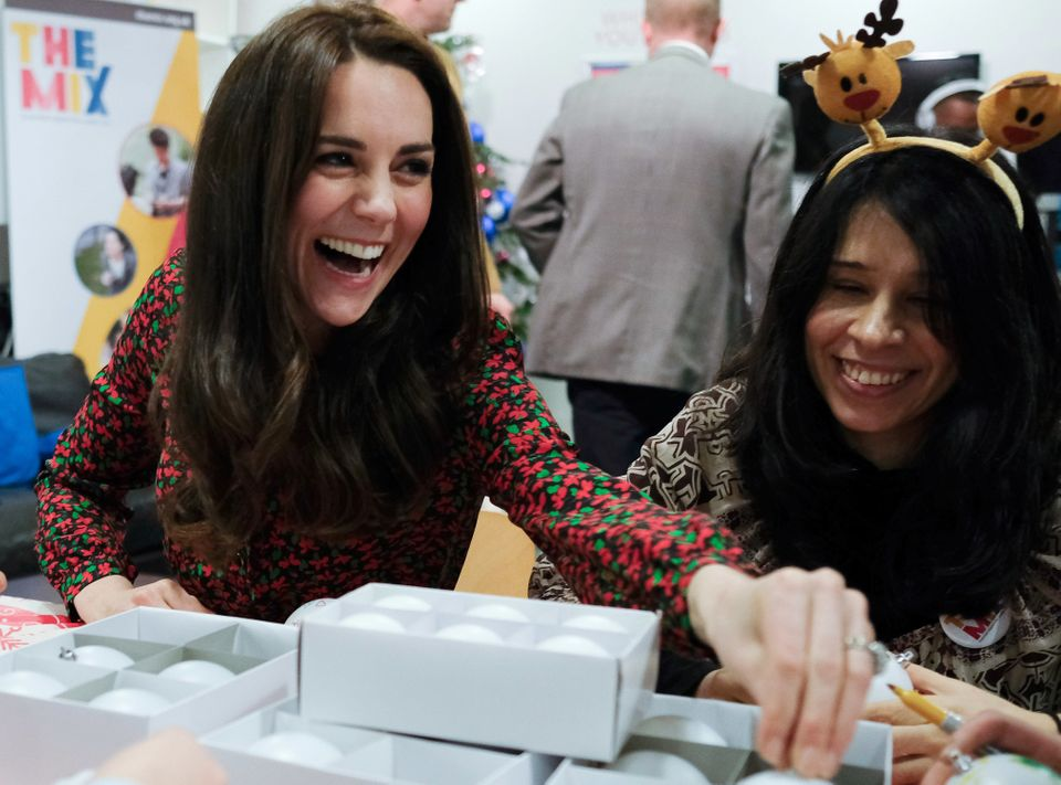 Catherine, Duchess of Cambridge smiles as he talks to staff and young people during a visit to a Christmas party for voluntee