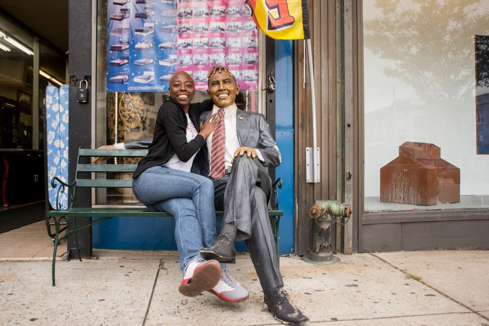 A womanwith a statue of Obama in front of furniture store Le Moda, 81 Market Street, Newark, New Jersey, 2016.