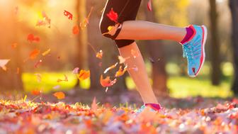 Close up of feet of woman runner running in autumn leaves, concept of training exercise