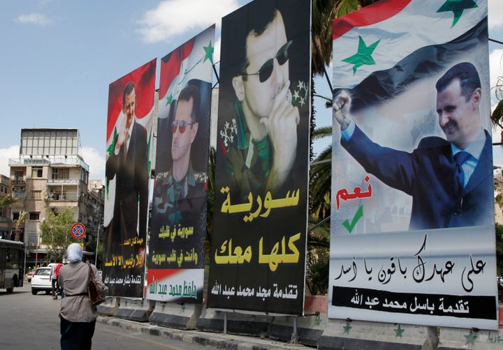 A woman walks past election posters of Syria's President Bashar Assad along a street in Damascus on June 2, 2014.